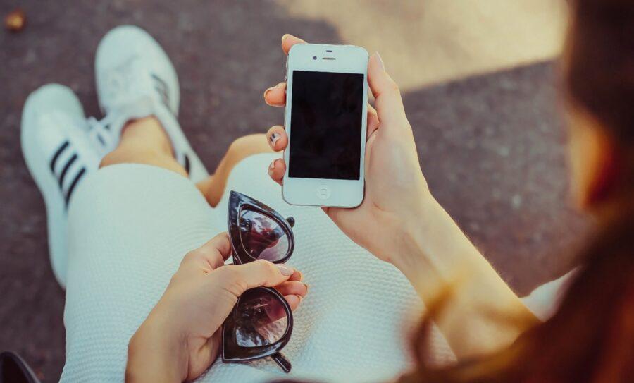 девушка держит очки и телефон