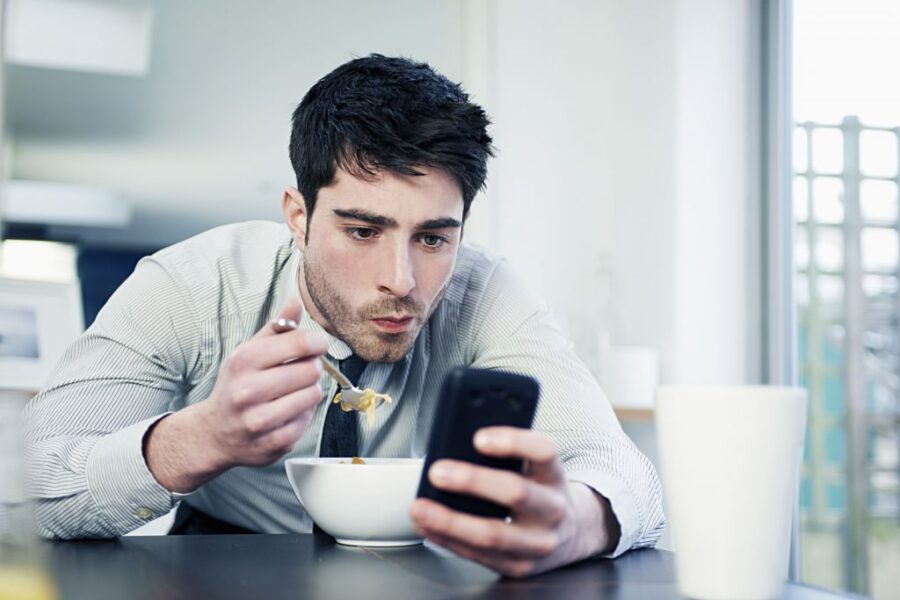 парень кушает с телефоном