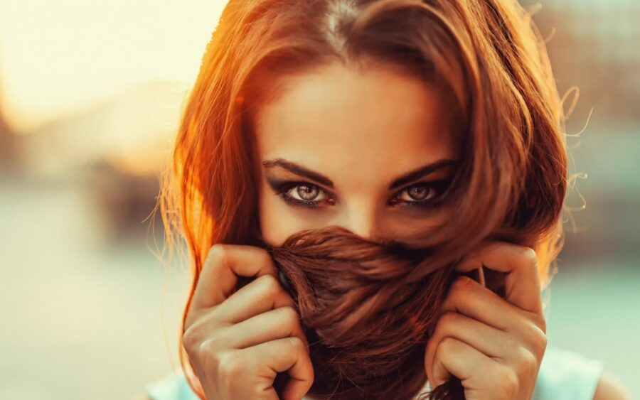 девушка прикрывает рот волосами