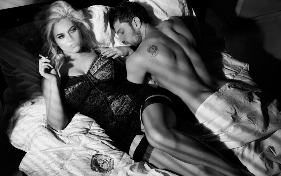 женщина курит в кровати с мужчиной