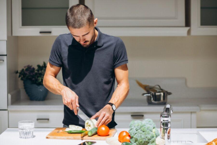 парень режет овощи