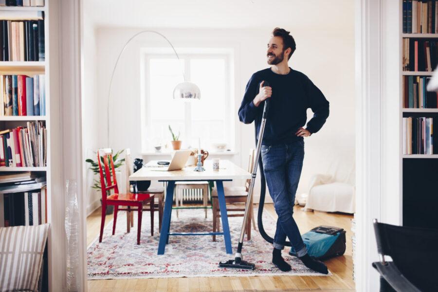 парень пылесосит дома