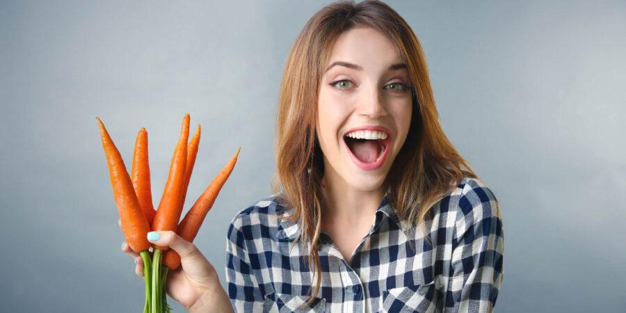 девушка держит морковки