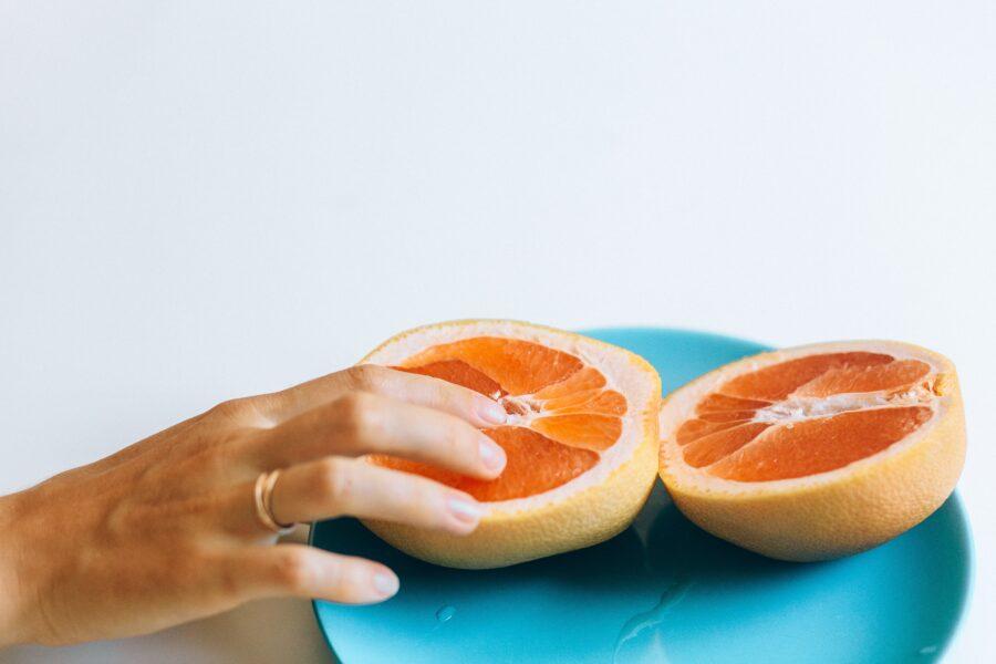 палец на половинке грейпфрута