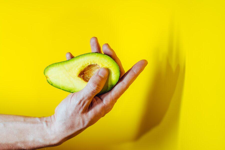 половинка авокадо в руке