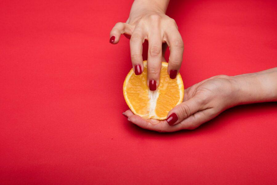 пальцы на половинке апельсина