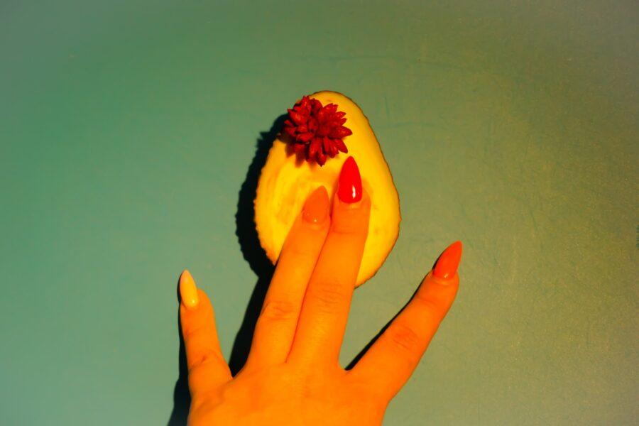 пальцы на половинке авокадо