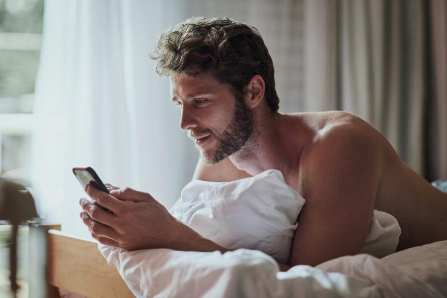 парень с телефоном в кровати
