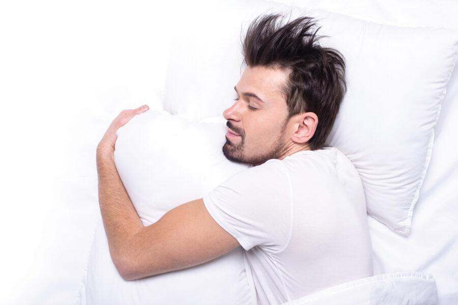 парень обнимает подушку