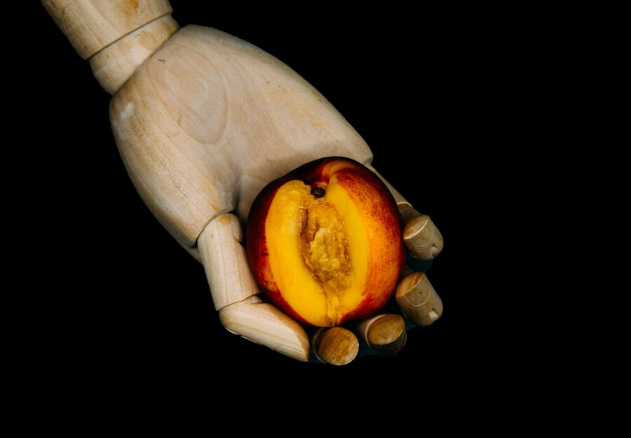персик в деревянной руке